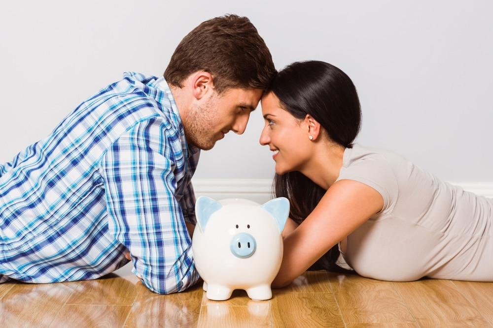 glückliches Paar mit Sparschwein