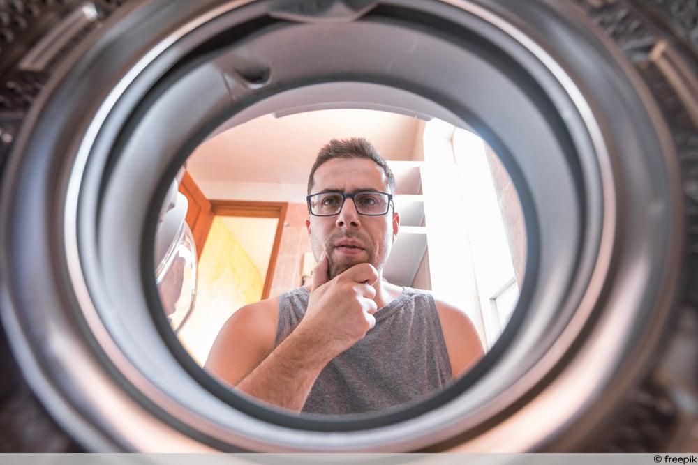 Mann schaut fragend in Waschmaschine