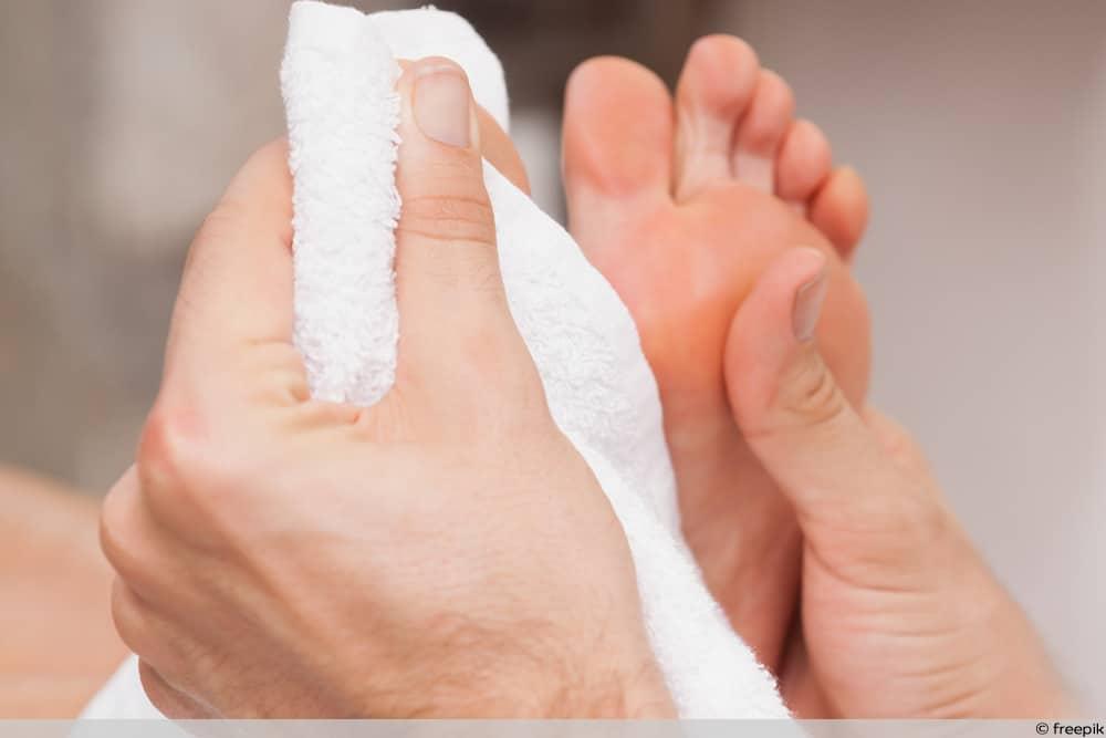 Ist Hautpilz ansteckend - Abtrocknen der Füße mit Handtuch