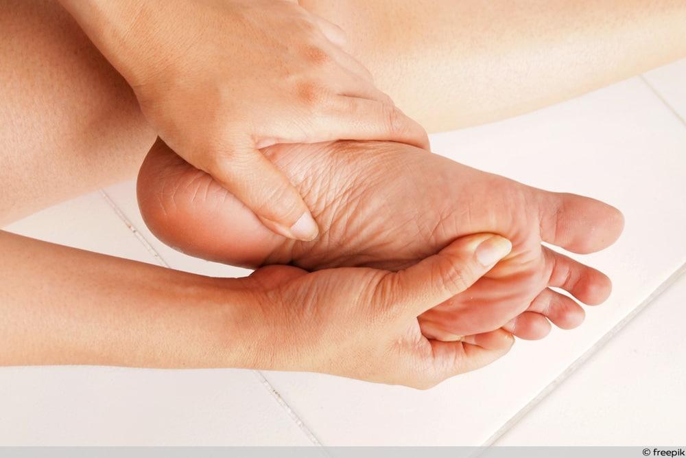 Frau greift sich an schmerzende Fußsohle