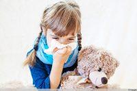 Kind mit grippalem Infekt niest in Taschentuch
