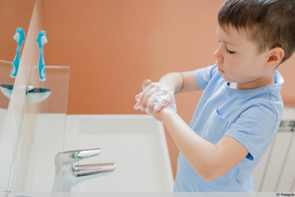 Kind wäscht Hände zur Vorbeugung