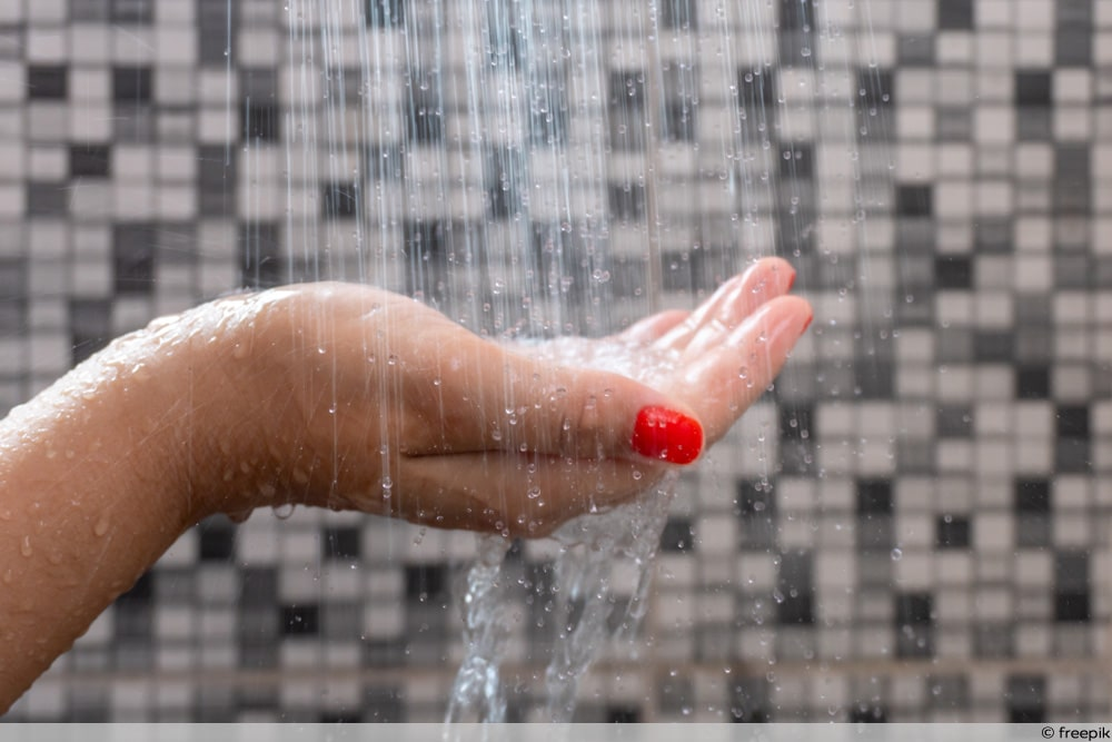 Frauenhand fühlt Duschstrahlen