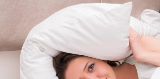 Frau in Bett mit Kissen über Kopf