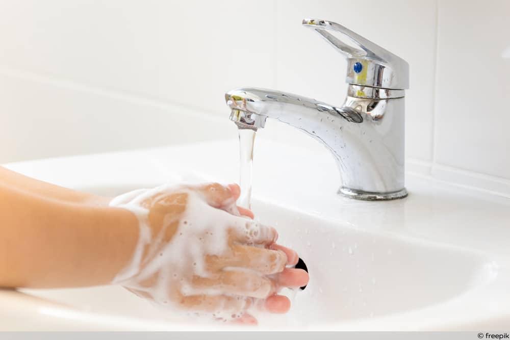 Wasserhahn spült Hände ab