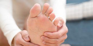 Frau hält sich Fuß