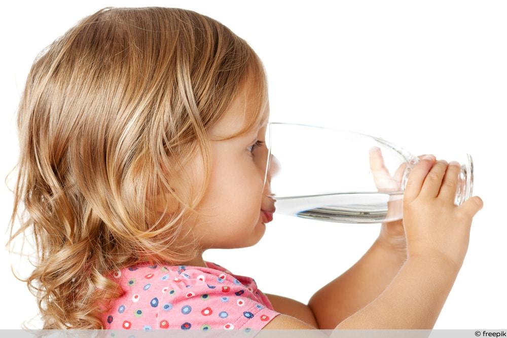 Kleinkind trinkt Glas Wasser