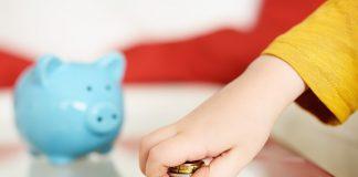Kind mit Geld in der Hand - Sparschwein im Hintergrund