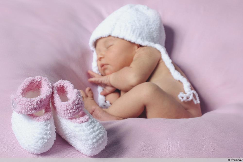 Baby im Bett mit Schuhen