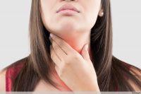 Frau hält sich Hals - Kehlkopfentzündung