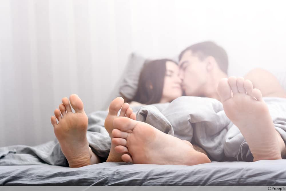 Pärchen kuschelnd im Bett