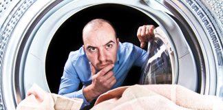 Mann schaut fragend in Waschmaschine hinein