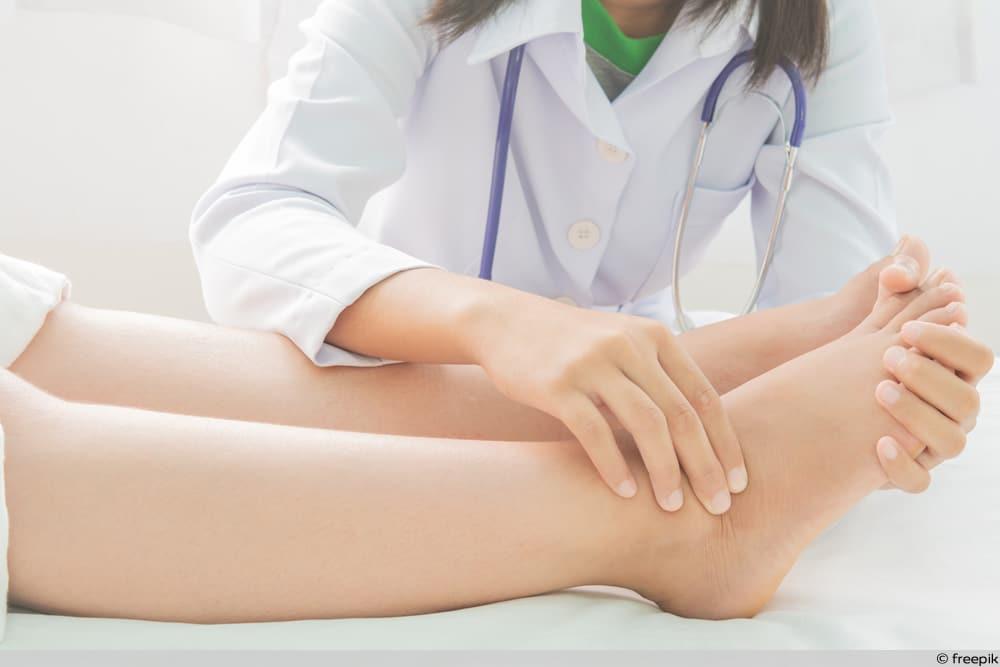 SSW 27 - Ärztin massiert geschwollene Füße einer Schwangeren