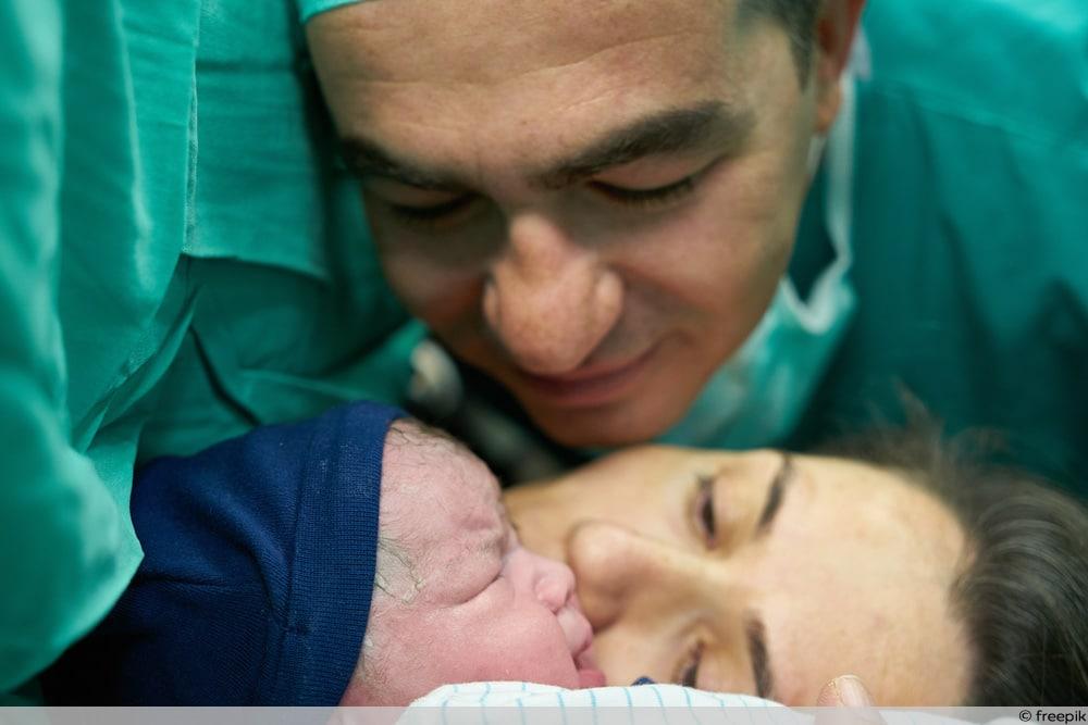 Vater bei der Geburt im Kreißsaal mit Neugeborenem