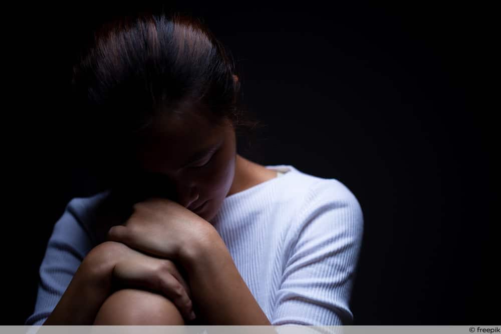 Depression durch Schuppenflechte - Frau im Dunkeln